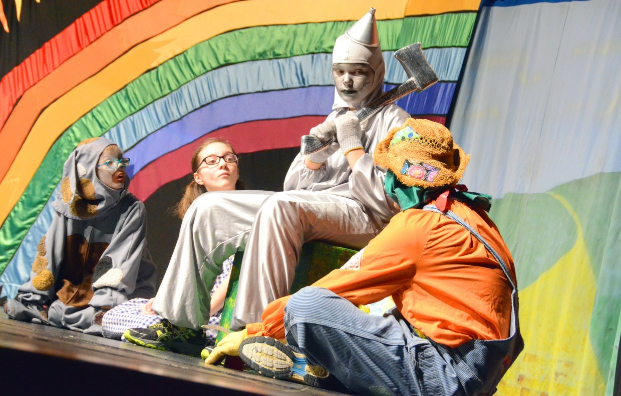"""The Tin Man (Braedyn Barton) tells his sad story to Toto (Rebekah Bolton), Dorothy (Rachel Bolton) and the Scarecrow (Chris Wilkinson) in the Missoula Children's Theatre production of """"The Wizard of Oz"""" Saturday afternoon in the Moffat County High School auditorium."""