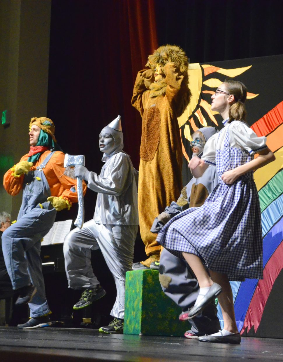 """The Cowardly Lion (Ryan Peck) shows his newfound confidence  with the help of the Scarecrow (Chris Wilkinson), the Tin Man (Braedyn Barton), Toto (Rebekah Bolton) and Dorothy (Rachel Bolton) in the Missoula Children's Theatre production of """"The Wizard of Oz"""" on Saturday afternoon in the Moffat County High School auditorium."""
