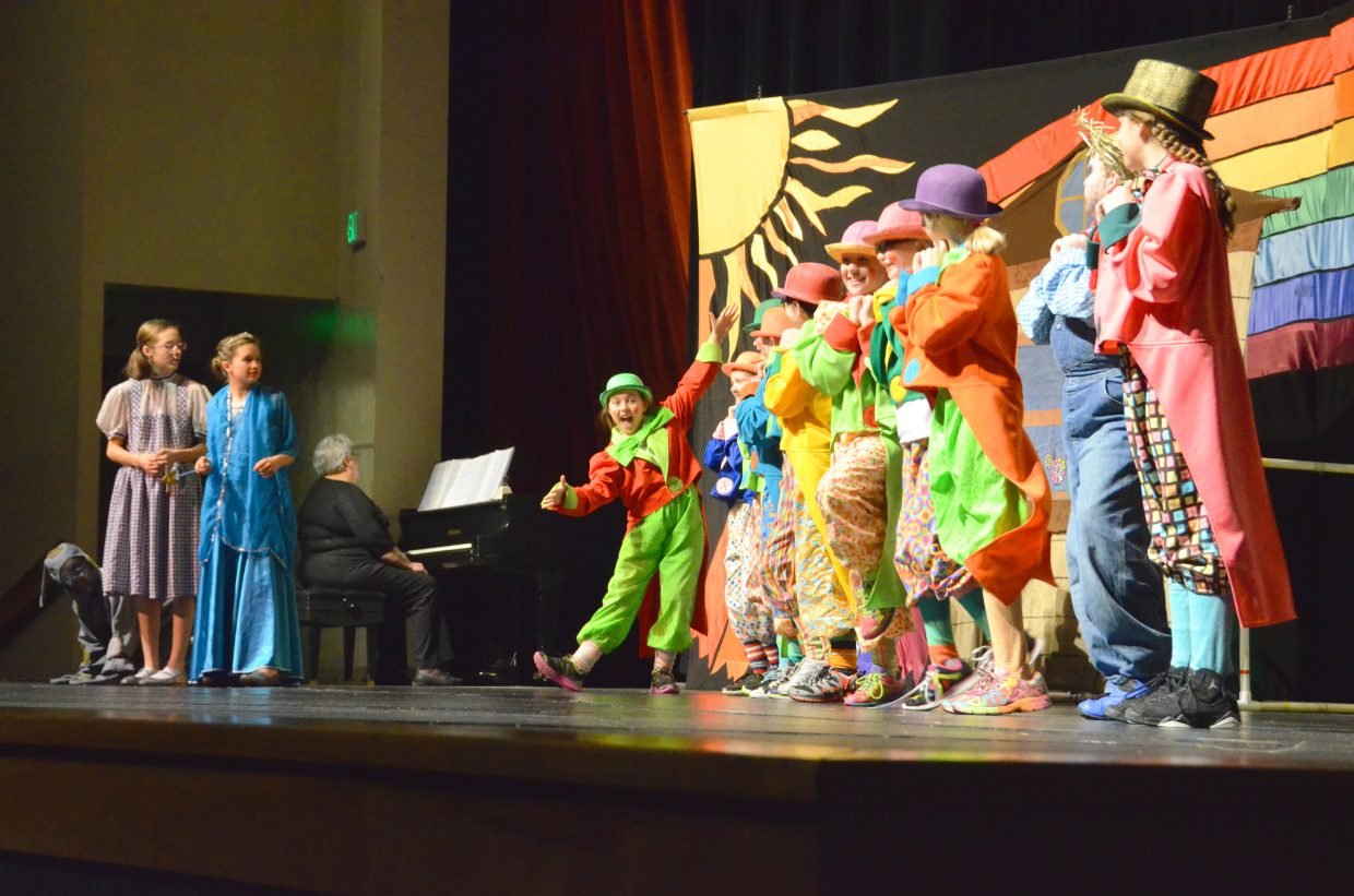 """The Munchkins introduce themselves to Dorothy (Rachel Bolton), Glinda the Good Witch (Emaleigh Papierski) and Toto (Rebekah Bolton) in the Missoula Children's Theatre production of """"The Wizard of Oz"""" Saturday afternoon in the Moffat County High School auditorium."""