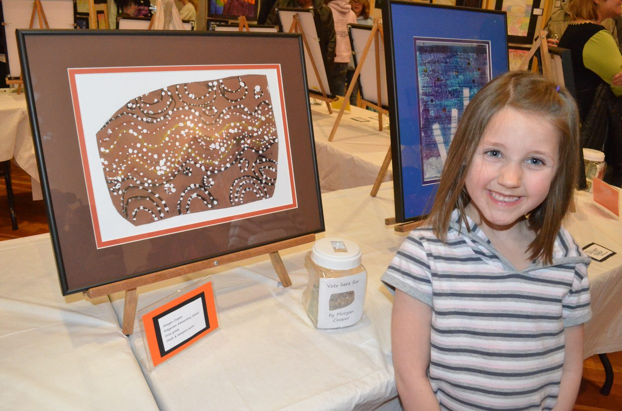 Ridgeview Elementary School first-grader Morgan Cooper, 6, stands proudly next to her artwork on display as one of the top 20 selections in the Cherish the Little Things Art Show. The show runs 2 to 6 p.m. Friday and 10 a.m. to 9 p.m. Saturday at Center of Craig, 601 Yampa Ave., as part of Saturday's Art Walk and Taste of Chocolate.
