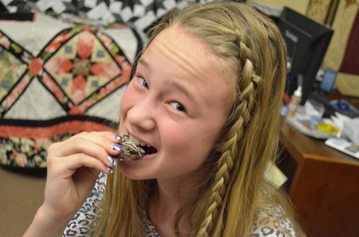 Sara Beason bites into a cluster of chocolate-covered pecans prepared by her mother, Renata, as part of the Art Walk and Taste of Chocolate Saturday in Craig. Chocolatiers, artists and musicians were spread across multiple downtown businesses.