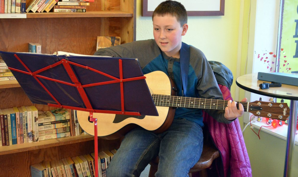 """Alexander Nichols, 11, strums and sings """"Sweet Home Alabama"""" in Downtown Books during the Art Walk and Taste of Chocolate Saturday. Nichols has played the instrument since he was 9."""