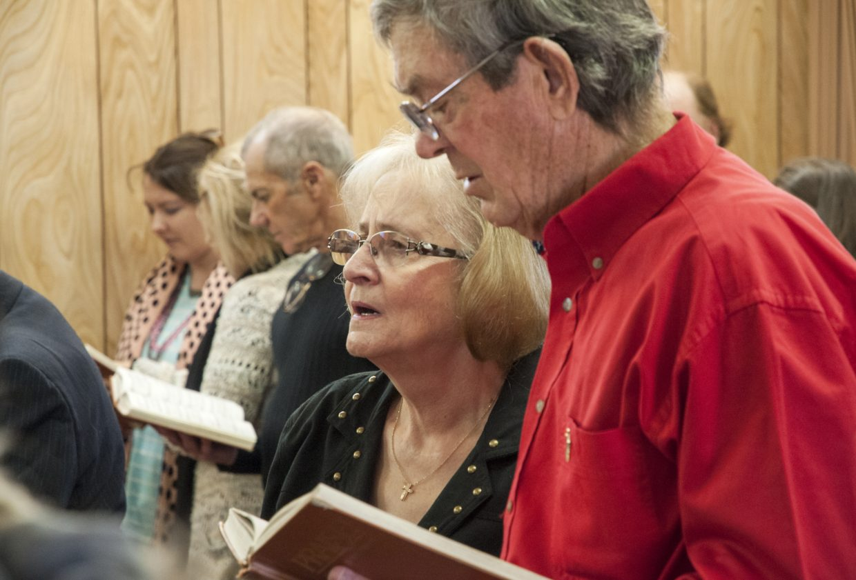 Pastor Linda Taylor joins her husband, Orval Taylor, in the pews to sign hymns during a Sunday service at Maybell Bible Church.