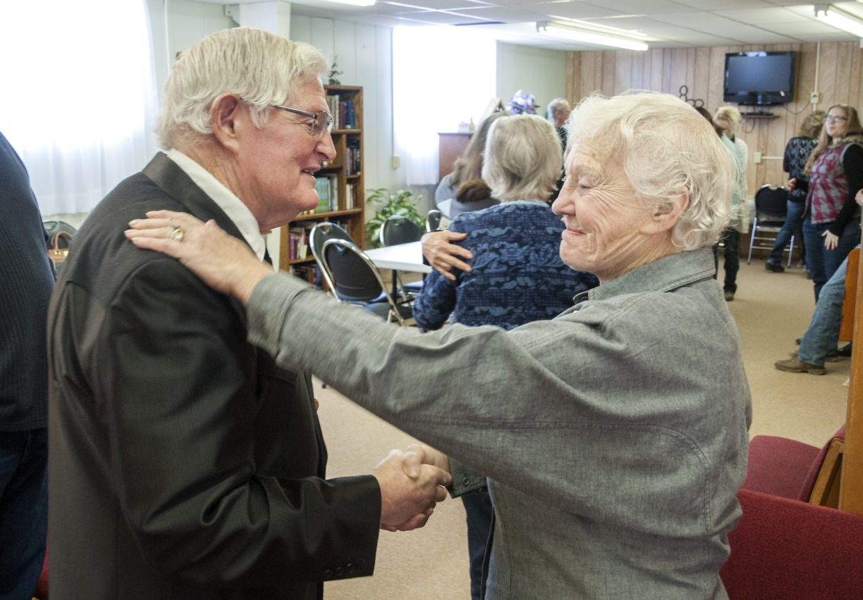 Bob Harding greets a fellow churchgoer at Maybell Bible Church after a Sunday morning service.