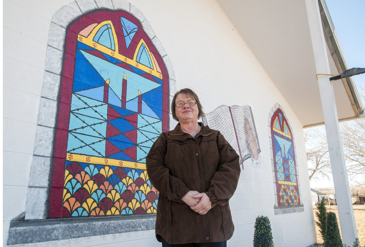 Judy Samer, owner of the Trav-O-Tel Motel in Craig, is the artist behind the new murals of stained glass windows and a bible on the north wall of the Maybell Bible Church.
