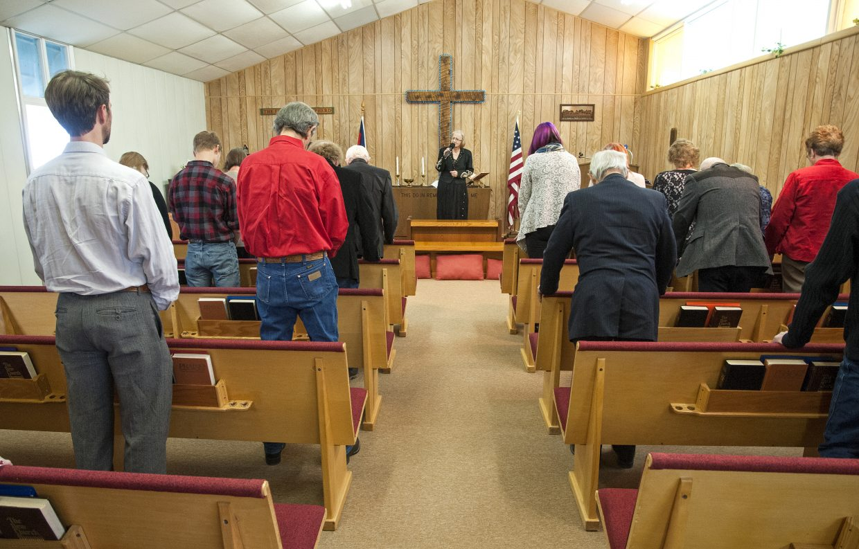 The congregation of Maybell Bible Church, led by Pastor Linda Taylor, stands to pray at the end of a Sunday service.