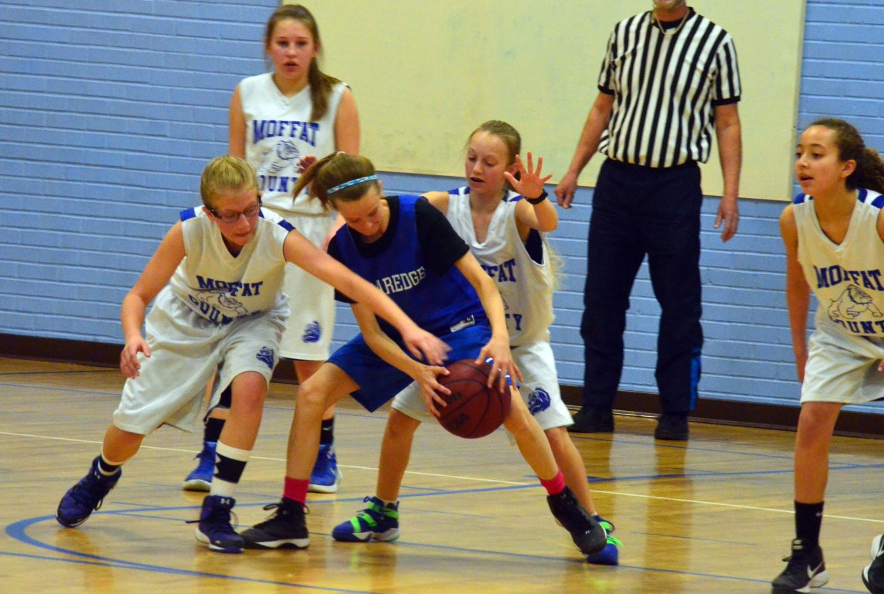 The Moffat County AAU seventh-grade girls basketball team plays intensive defense against Cedaredge Saturday. The team won twice against Cedaredge and lost to the Montrose eighth-graders during a weekend home tournament.