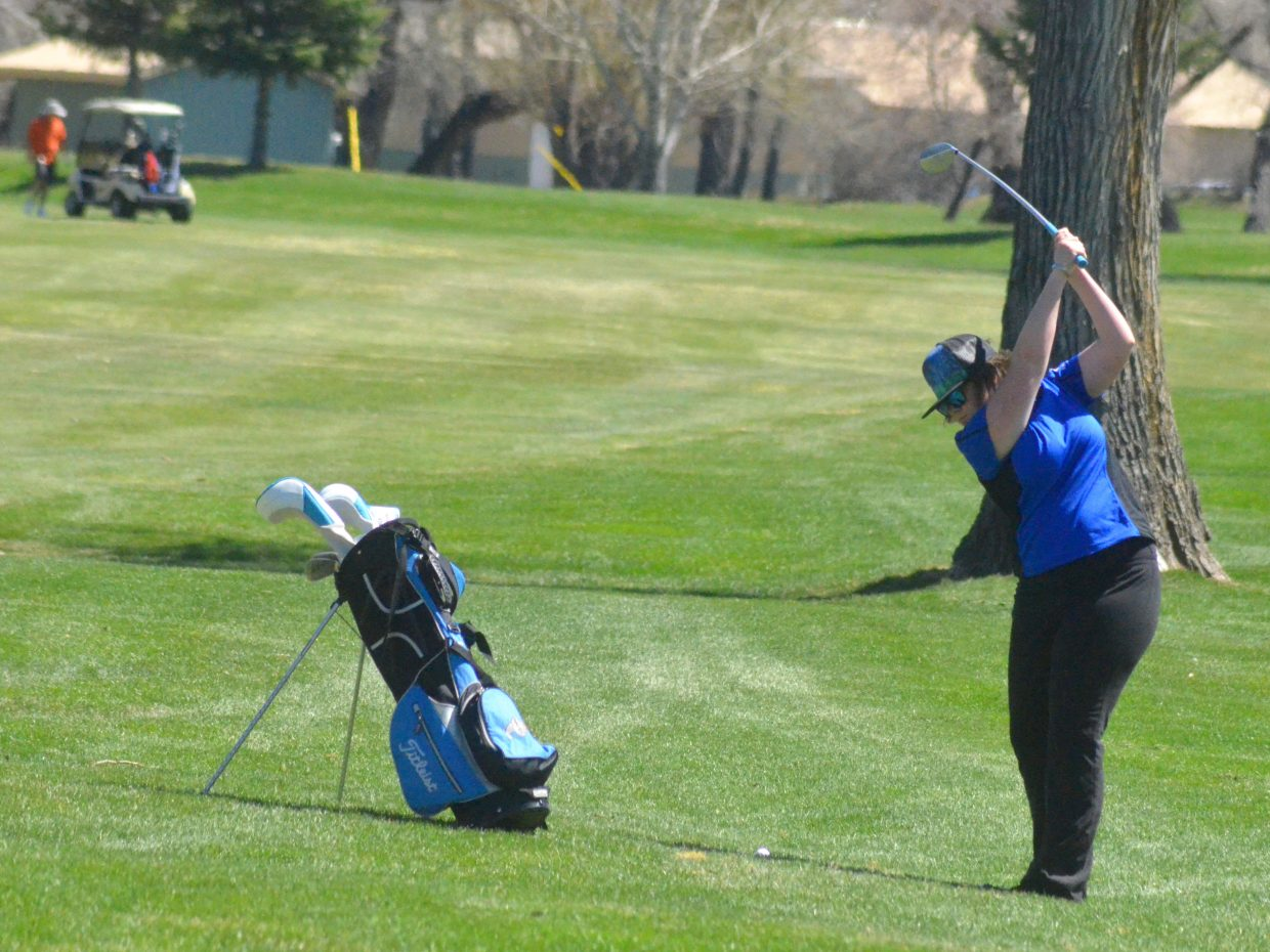 Moffat County High School's Tané Otis goes into her backswing to hit from the rough of the first fairway at Yampa Valley Golf Course.