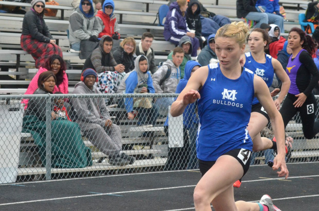 Moffat County High School's Kayla Pinnt, foreground, speeds ahead of the competition with younger sister Quinn close behind in the 100-meter dash. Kayla won both the 100 and 200 races during Friday's Clint Wells Invitational at MCHS.