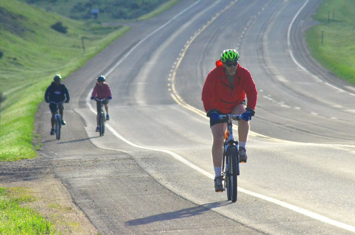 """Cyclists get in gear after completing a slope along US Highway 40 as part of Saturday morning's """"Where the Hell's Maybell?"""""""