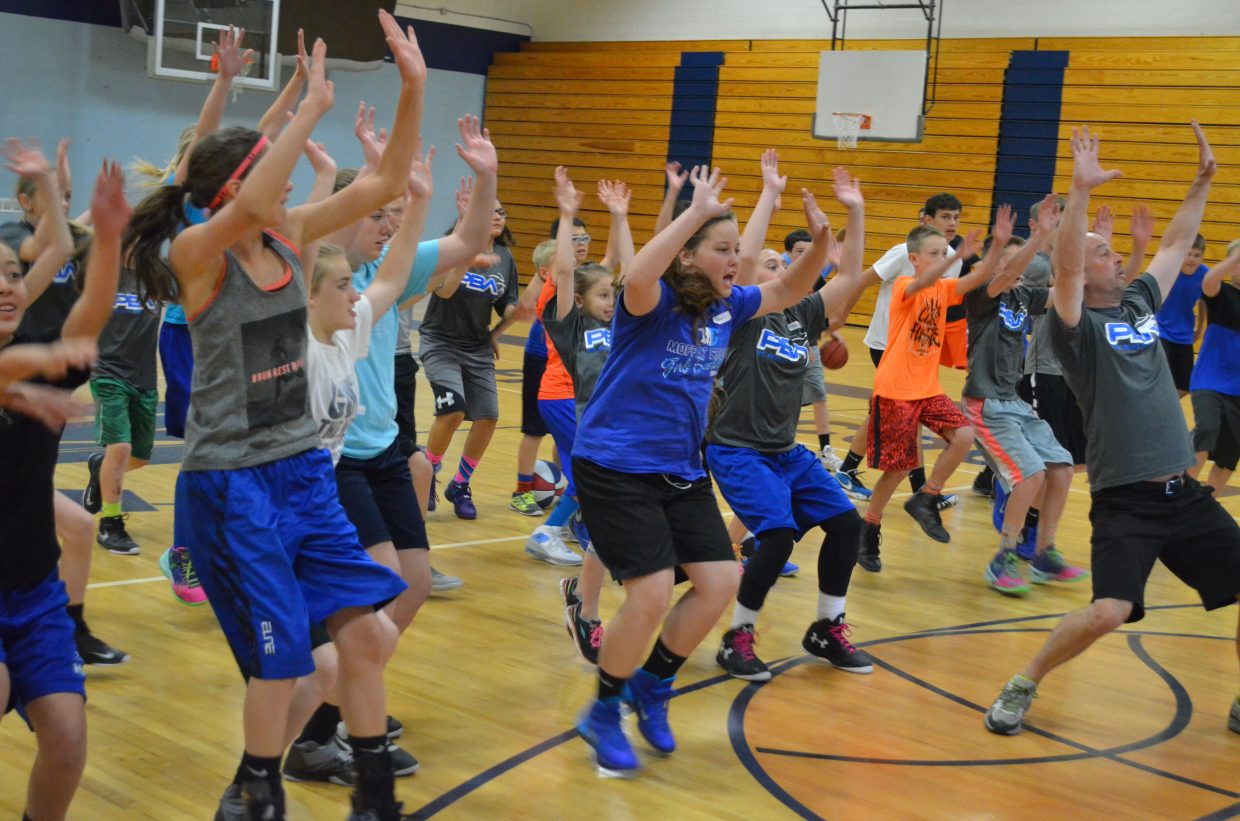 Mike Moskowitz leads players in a demonstration of putting their arms up and blocking opponents' shots during a session of the Progressive Basketball Academy in the Moffat County High School gym.