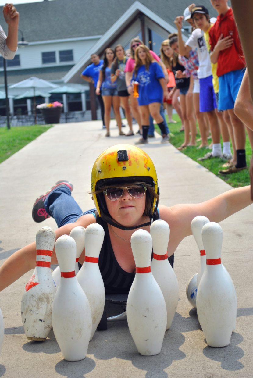 Tané Otis gets a strike as part of the human bowling activity at Castaway Club Young Life Camp.