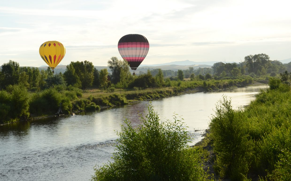 Two balloons fly low over the Yampa River north of Loudy-Simpson Park.