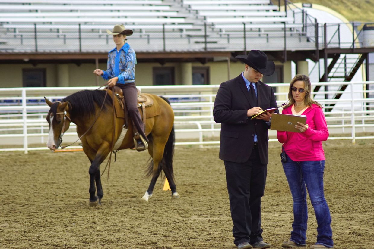 Western Horse Show judge and assistant tally scores while a mounted competitor waits for results.