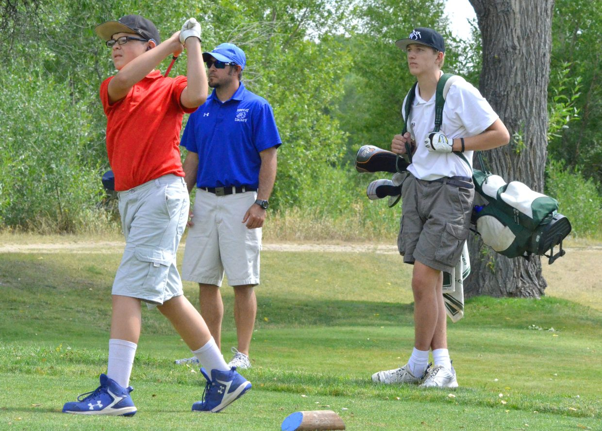 From left, Moffat County High School freshman James DeWald drives from the eighth tee box of Yampa Valley Golf Course Monday as MCHS coach Justin Folley and Rangely's Marshall Webber observe. The Bulldogs had three varsity and two JV golfers in the MCHS Invitiational among 69 players and 11 schools.