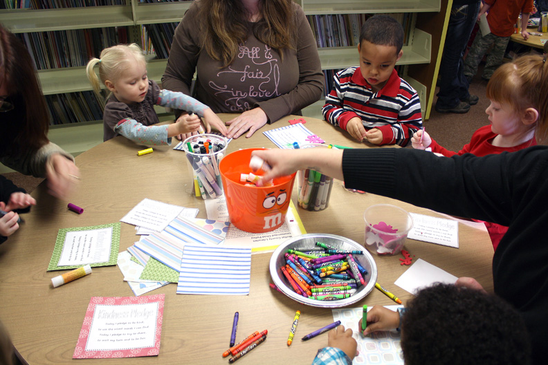 Shelbe Cox, 2, Treavon Wilson, 2, and Jaclyn Pershall, 3, color together at a table after story time.