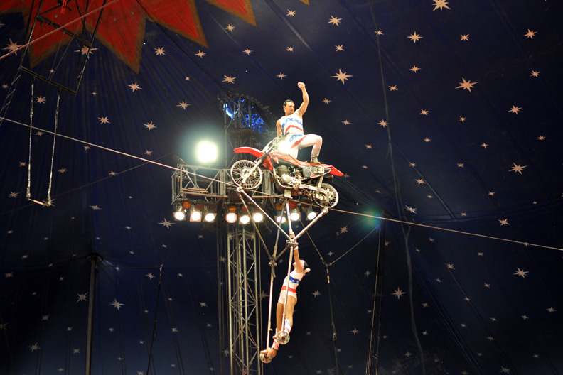 A Carson and Barnes Circus performer pauses atop a motorcycle balanced on a high wire as an acrobat hangs suspended above the crowd Tuesday at the Moffat County Fairgrounds.