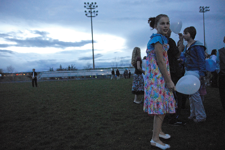 Craig Middle School seventh-grader Makenna Reidhead stands on the Moffat County High School football field Thursday during a balloon release in honor of CMS band teacher Craig Smith.