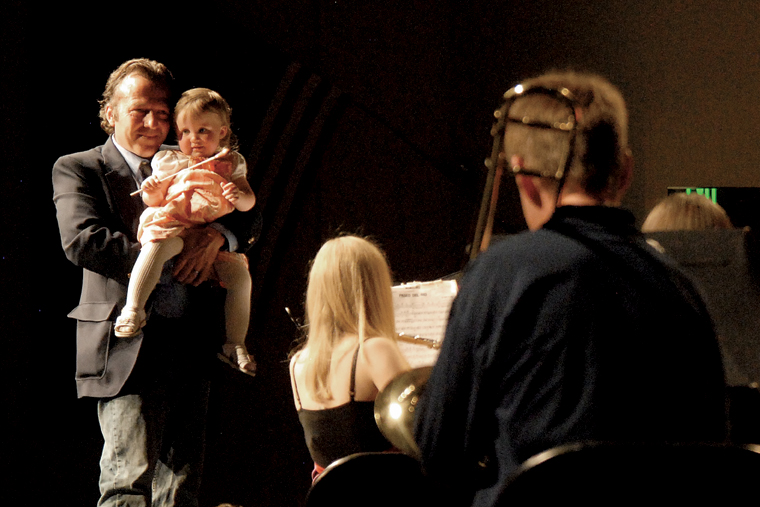 "Deron Smith holds his daughter, Isabella Marie Smith, onstage Thursday at the Moffat County High School auditorium. Deron is the son of the late Craig Middle School band teacher Craig Smith, and Isabella is Craig's granddaughter. Craig Smith, a popular instructor at the middle school, died Sunday. Isabella ""conducted"" the final song of Thursday's concert, which was a tribute to her grandfather."