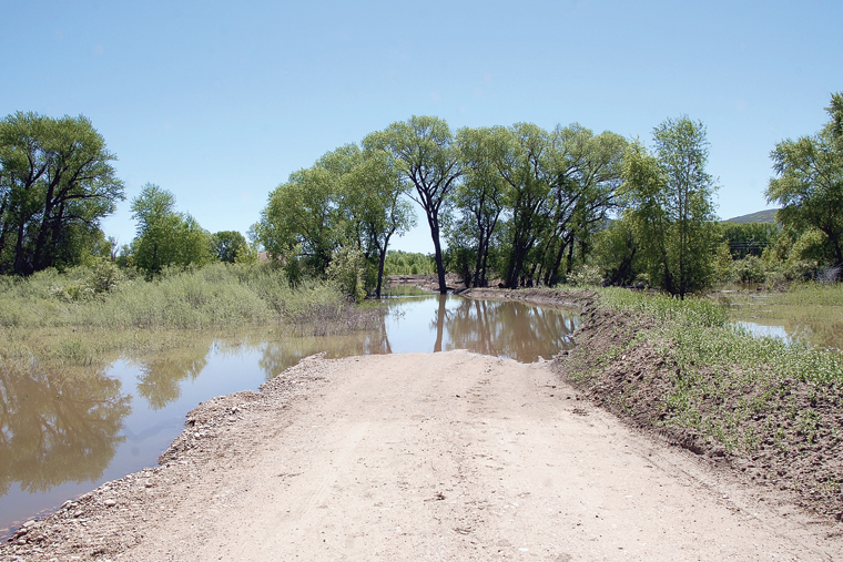 A dirt road toward a gravel pit at Northwest Ready Mix in Craig is flooded. Co-owner Roger Simones said the flooding this year is as bad as he's seen.