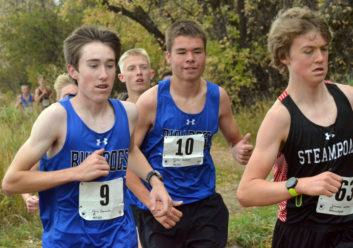 Moffat County High School cross country runners Chris Carrouth, left, and Carter Severson look to edge past Steamboat Springs competition on the Nature Trail during the Bulldog Invitational Saturday at Loudy-Simpson Park.