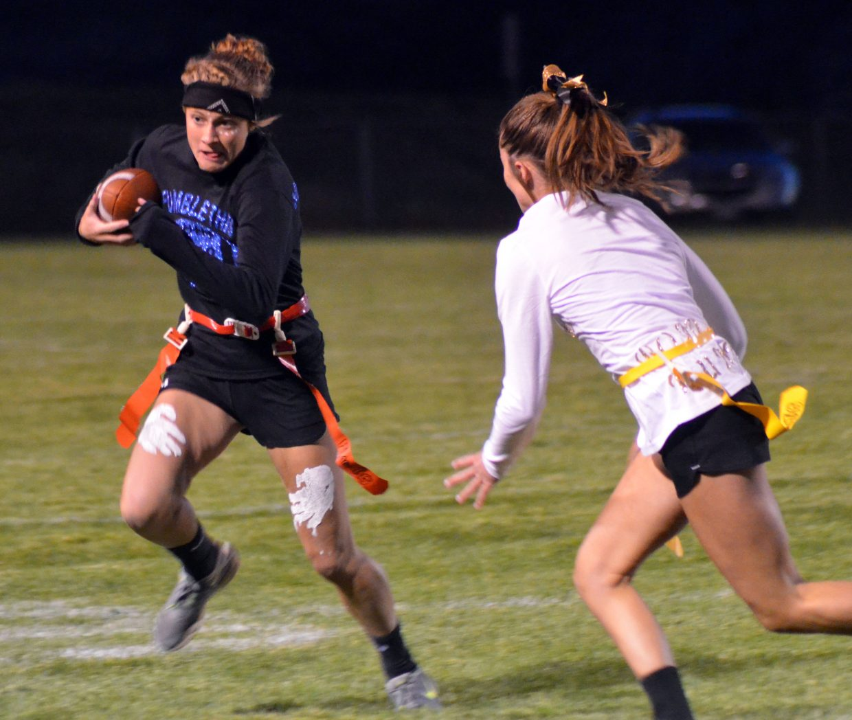 Kelsey McDiffett of Blitz Babes tucks the ball as she sweeps wide during the Powder Puff Football tournament Wednesday night at Moffat County High School.