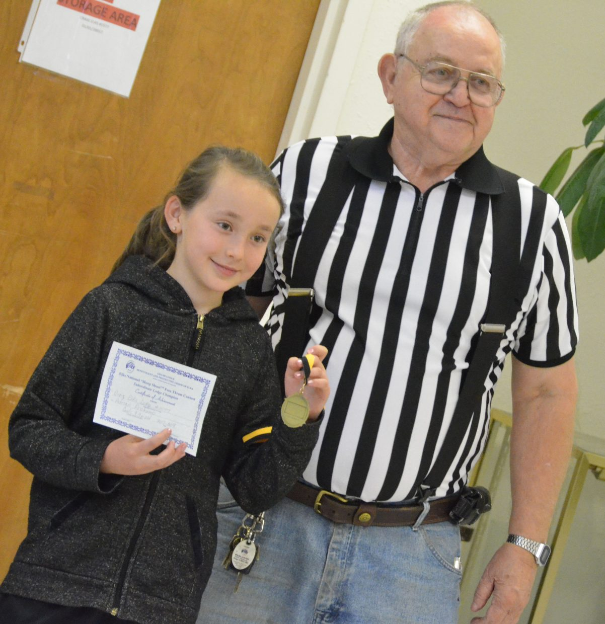 Frank Sadvar provides Adrian Profumo a first-place medal as the local winner of 8- and 9-year-old girls winner of the Elks National Hoop Shoot Free Throw Contest.