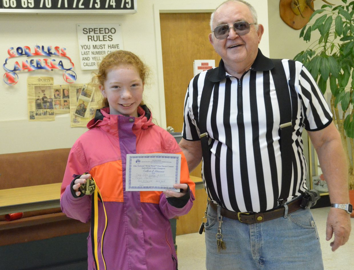 Frank Sadvar provides Teryn Carter a first-place medal as the local winner of 10- and 11-year-old girls winner of the Elks National Hoop Shoot Free Throw Contest.