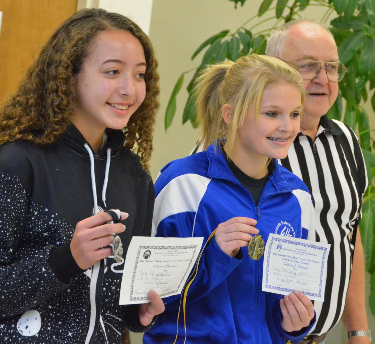 From left, Olivia Profumo and Jacie Evenson display second- and first-place medals provided by Frank Sadvar as the local winners of the  12- and 13-year-old division of the Elks National Hoop Shoot Free Throw Contest.