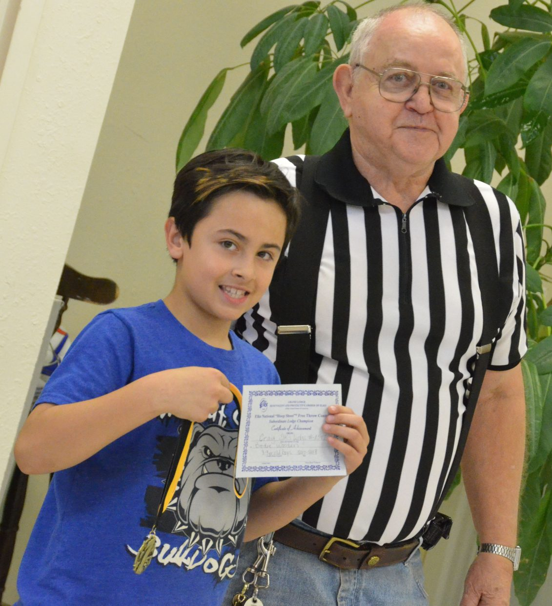 Frank Sadvar provides Brodie Wooden his first-place medal as the local winner of 8- and 9-year-old boys winner of the Elks National Hoop Shoot Free Throw Contest.