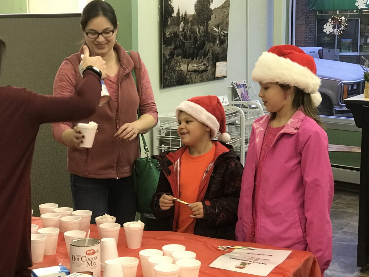 A local family is served hot chocolate and cookies by the Bank of Colorado, which kindly agreed to assist Santa Claus during the annual Letters to Santa event, held Wednesday at the Craig Press.