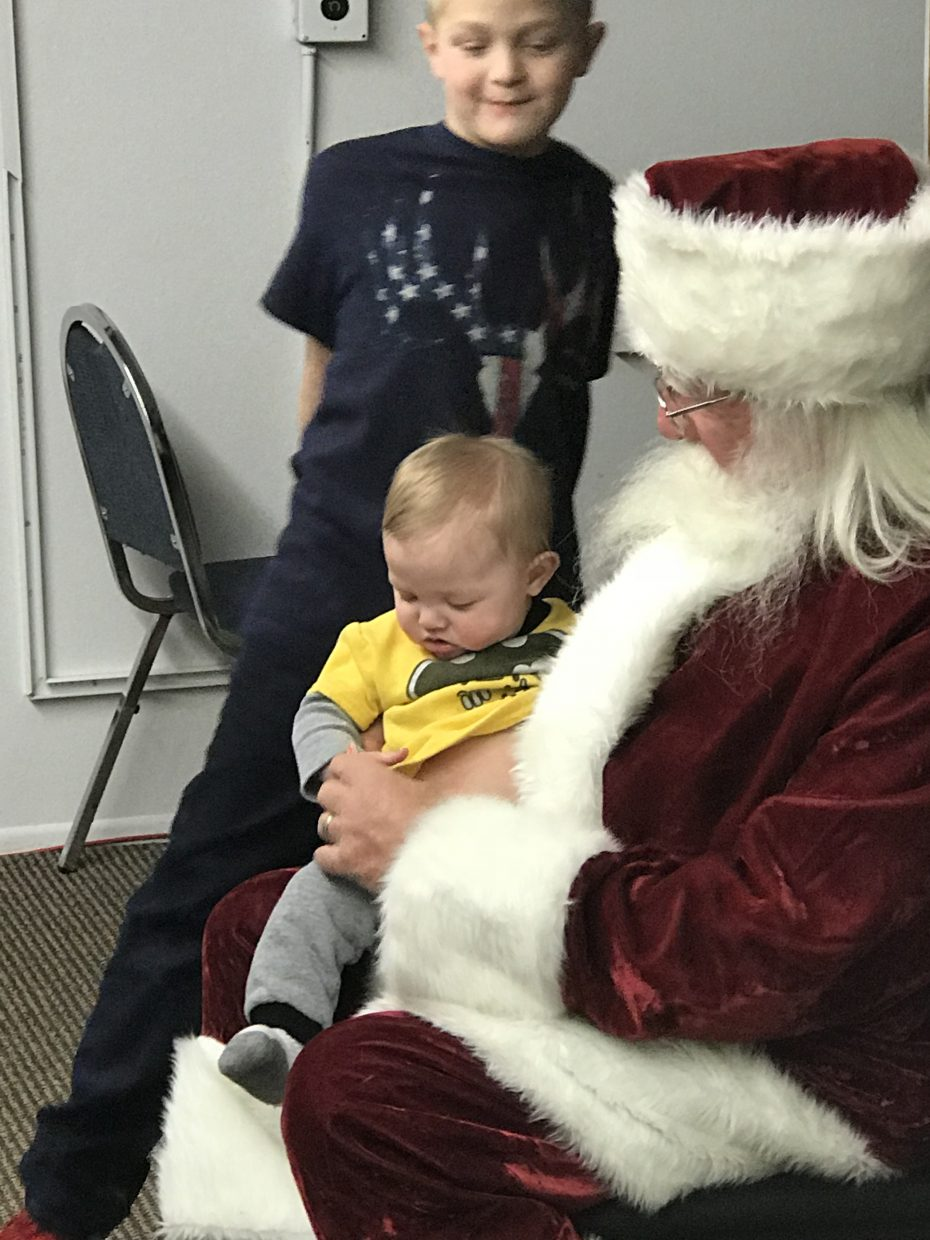 Santa Claus has a chat with one of his youngest fans during the annual Letters to Santa event, held Wednesday at the Craig Press.