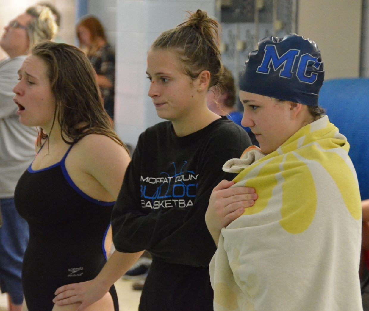 From left, Molly Neton, Kelsey McDiffett and Katelynn Turner provide encouragement for teammates during the Moffat County Meet.