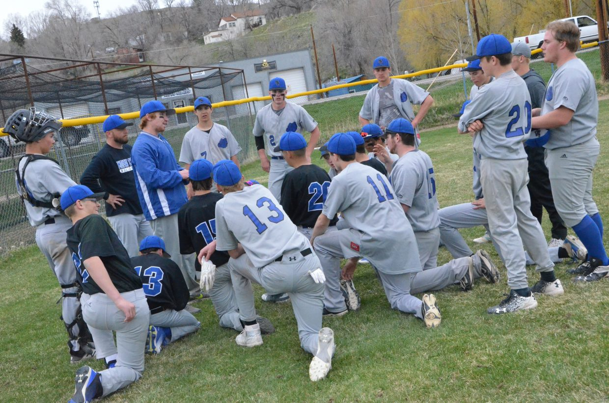 Moffat County High School baseball players kneel for a post-game pep talk from coaches after a win over Grand Valley.
