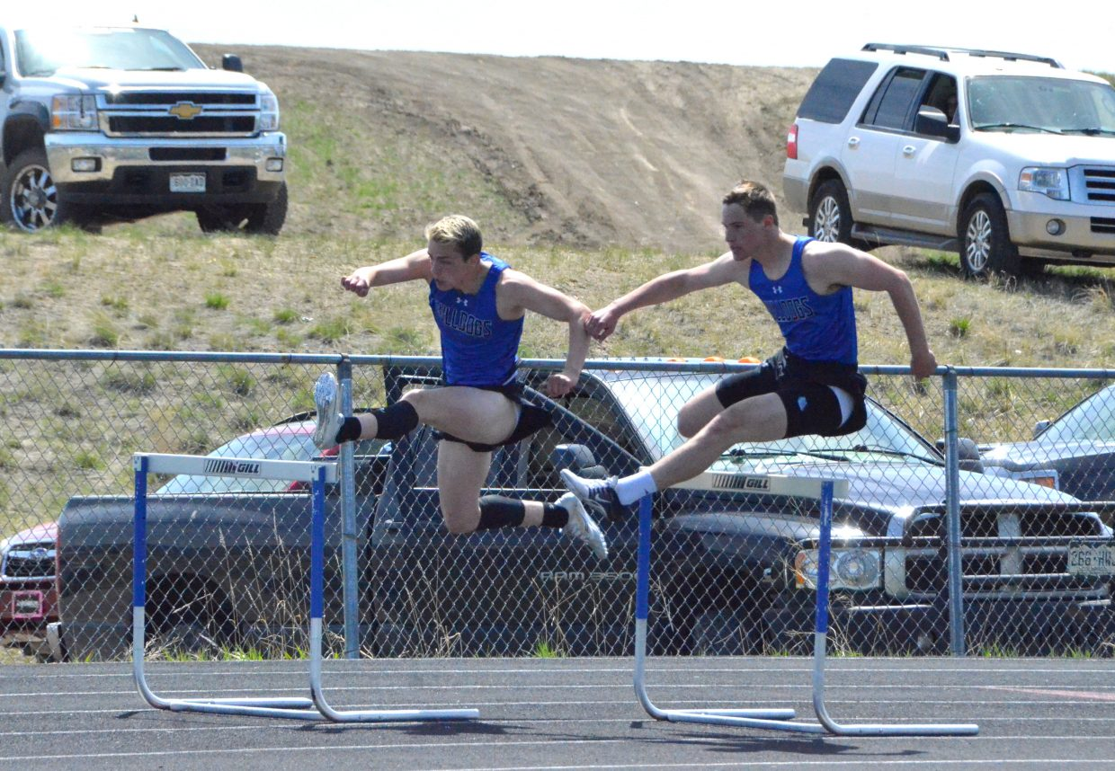 Moffat County High School's Jared Atkin, left and Miki Klimper stay in sync on the curve of the boys 300-meter hurdles Friday at the Clint Wells Invitational.