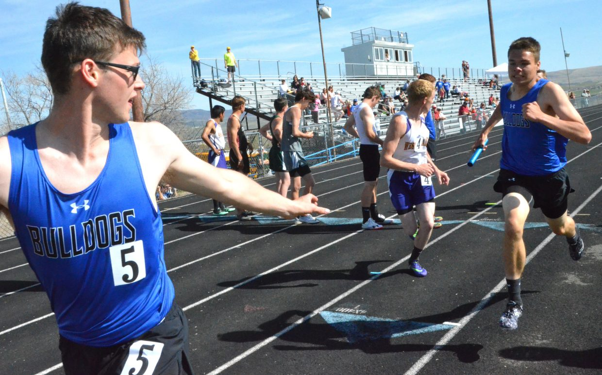 Moffat County High School's Colin Jensen left, takes his first few steps for the final lap as teammate Carter Severson approaches with the baton during the boys 4x400-meter relay Friday at the Clint Wells Invitational.