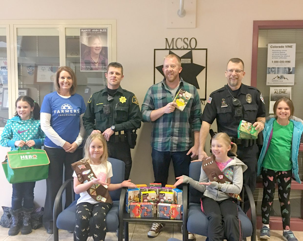 Law enforcement officers receive a sweet treat as Girl Scouts deliver 25 boxes of cookies to the Public Safety Center in Craig in early March.