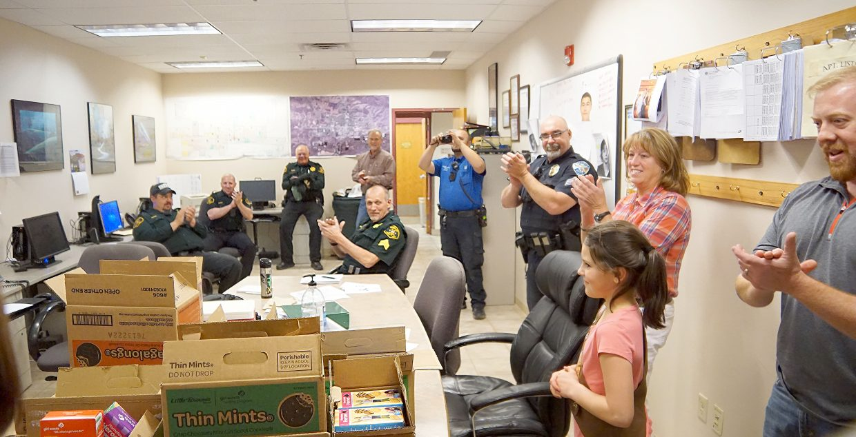 Local law enforcement officers applaud the Girl Scouts of Troop 16185.