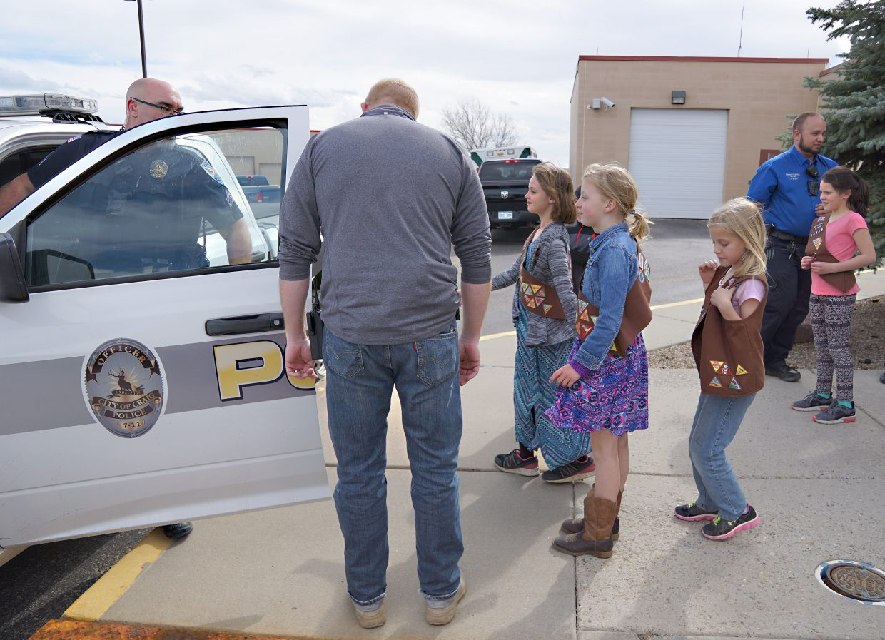 Officer Grant Laehr and Sergeant Anthony Fandel invite the Girl Scouts of Troop 16185 to take a closer look at the inside of one of the trucks used by the Craig Police Department.