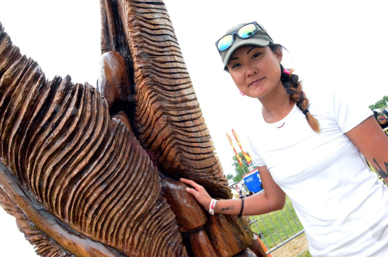 Justine Park of Boulder takes a reflective moment with her carving
