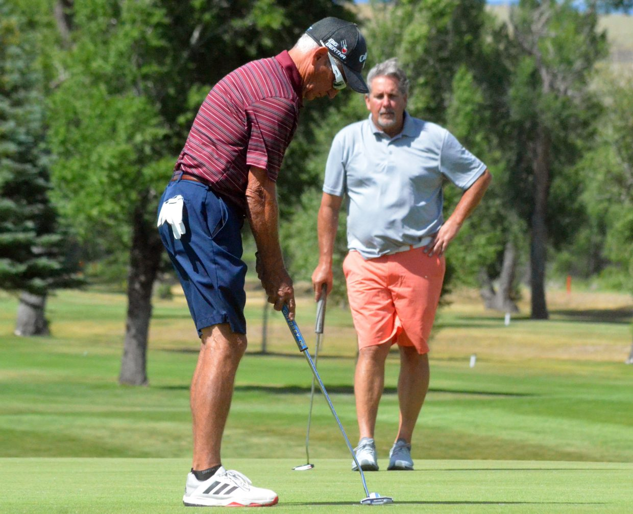 Pete Heuer looks on as Delta's Ron Alberts putts for birdie on the 18th green to finish out his first day of the 51st annual Cottonwood Classic at Yampa Valley Golf Course.