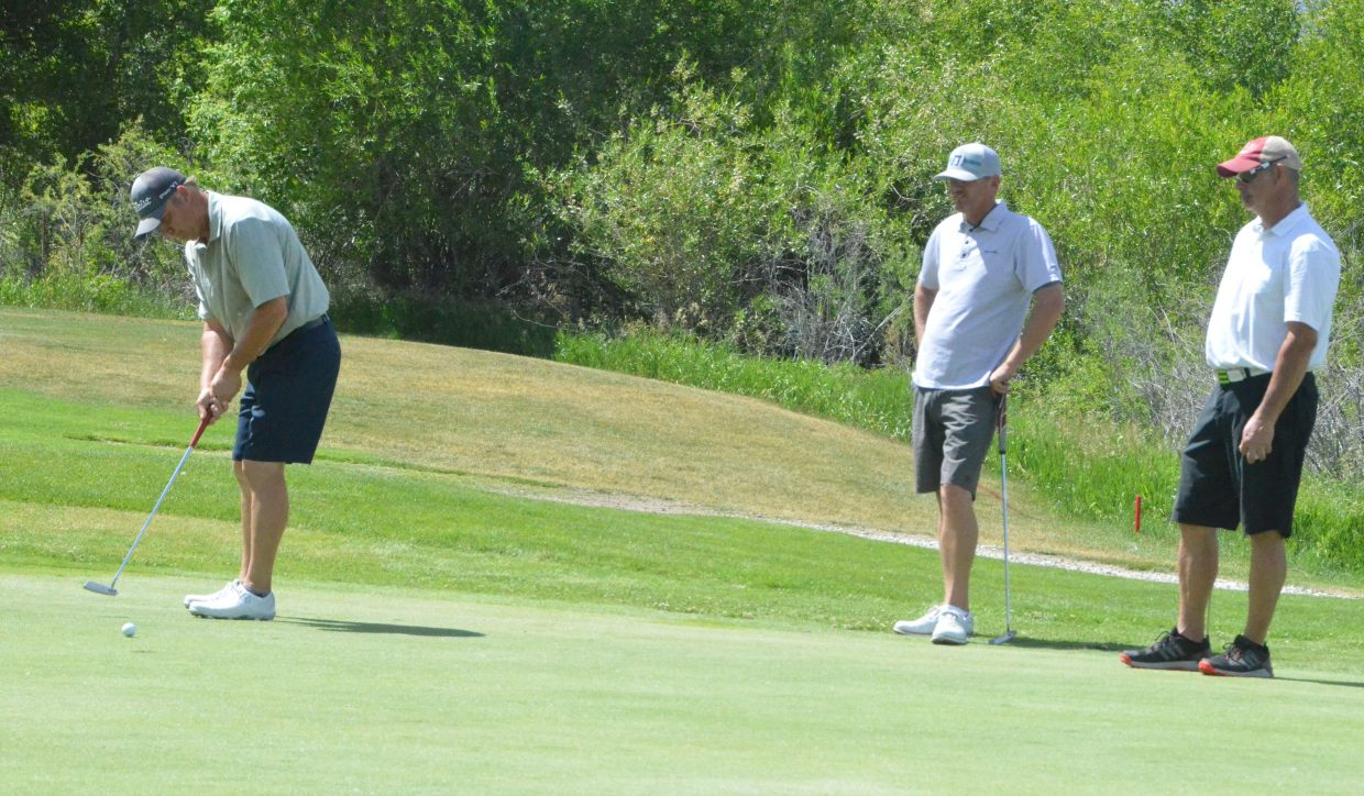 Grand Junction's Dave Lawien, left, lines up his putt as fellow golfers Craig Nichols, of Glenwood Springs and Steamboat Springs' Ernie Thiel, watch on the 13th green during the first day of the 51st annual Cottonwood Classic at Yampa Valley Golf Course.