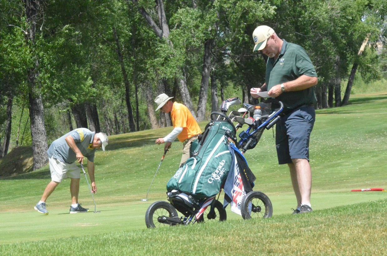 Roxborough's Mike Gardner, right, marks his score card while New Castle's Danny Adams and Steamboat Springs' Jeff Nelson finish up on the 15th green Saturday at the 51st annual Cottonwood Classic at Yampa Valley Golf Course.