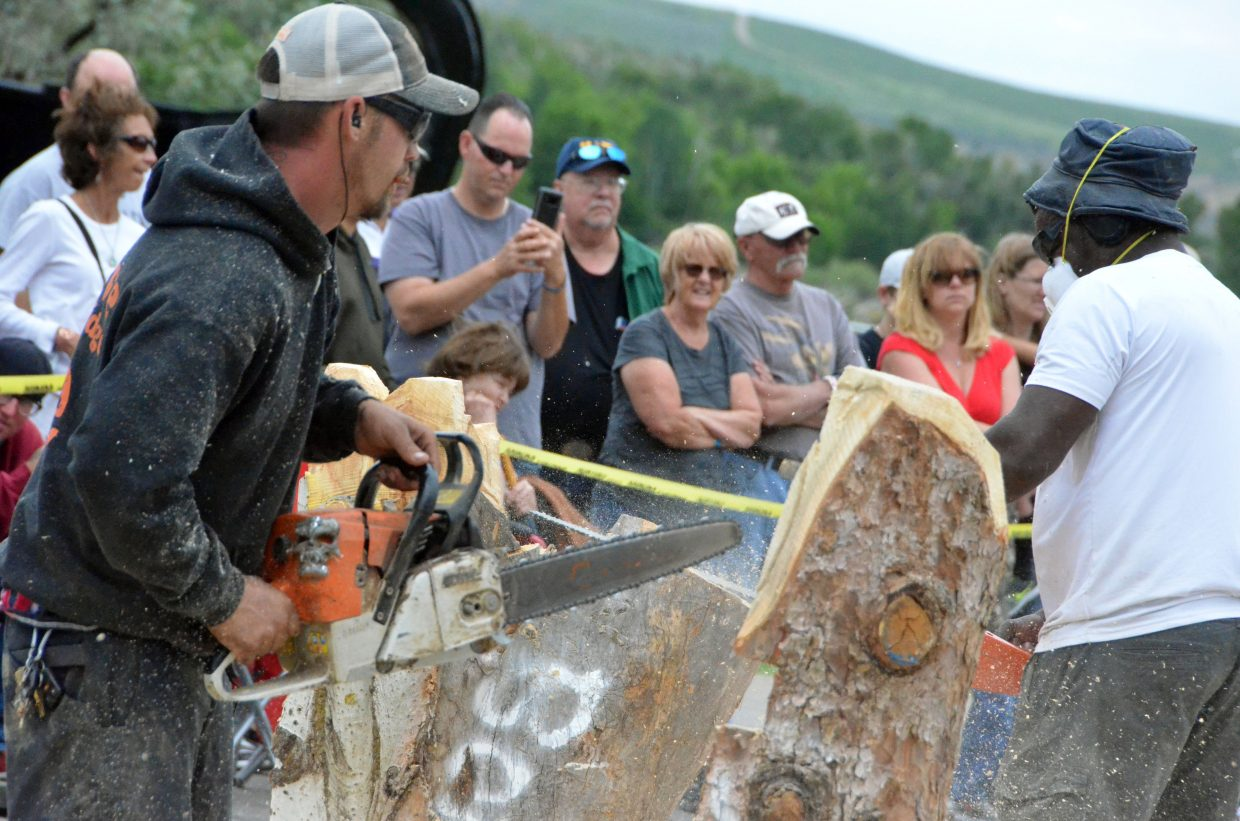 Spectators watch as carvers Damon Gorecki, left, and Bongo Love compete Saturday during the Quick Carve competition at the 19th annual Whittle the Wood Rendezvous.