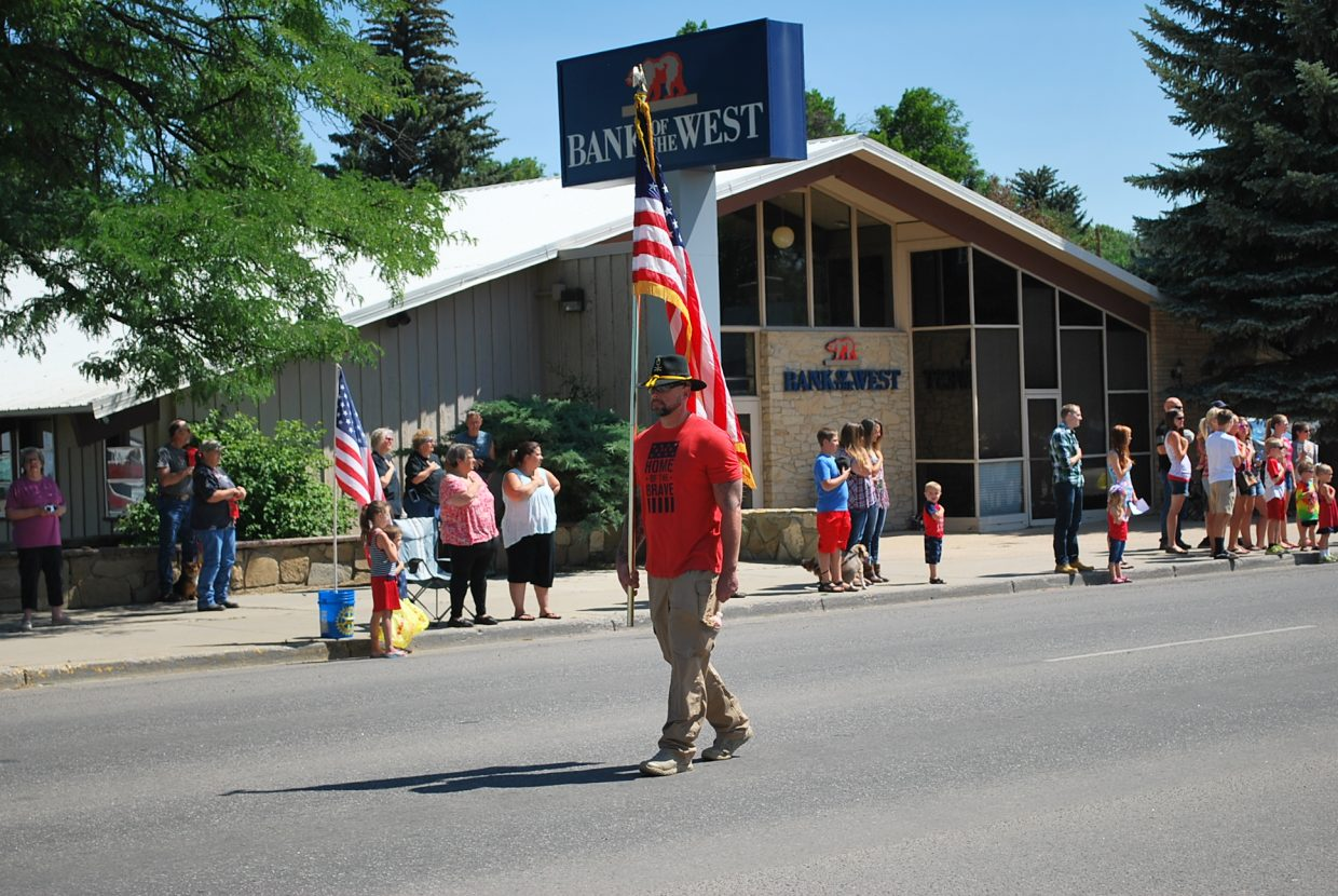 A lone flag bearer carries the stars and stripes as parade floats follows shortly behind him.