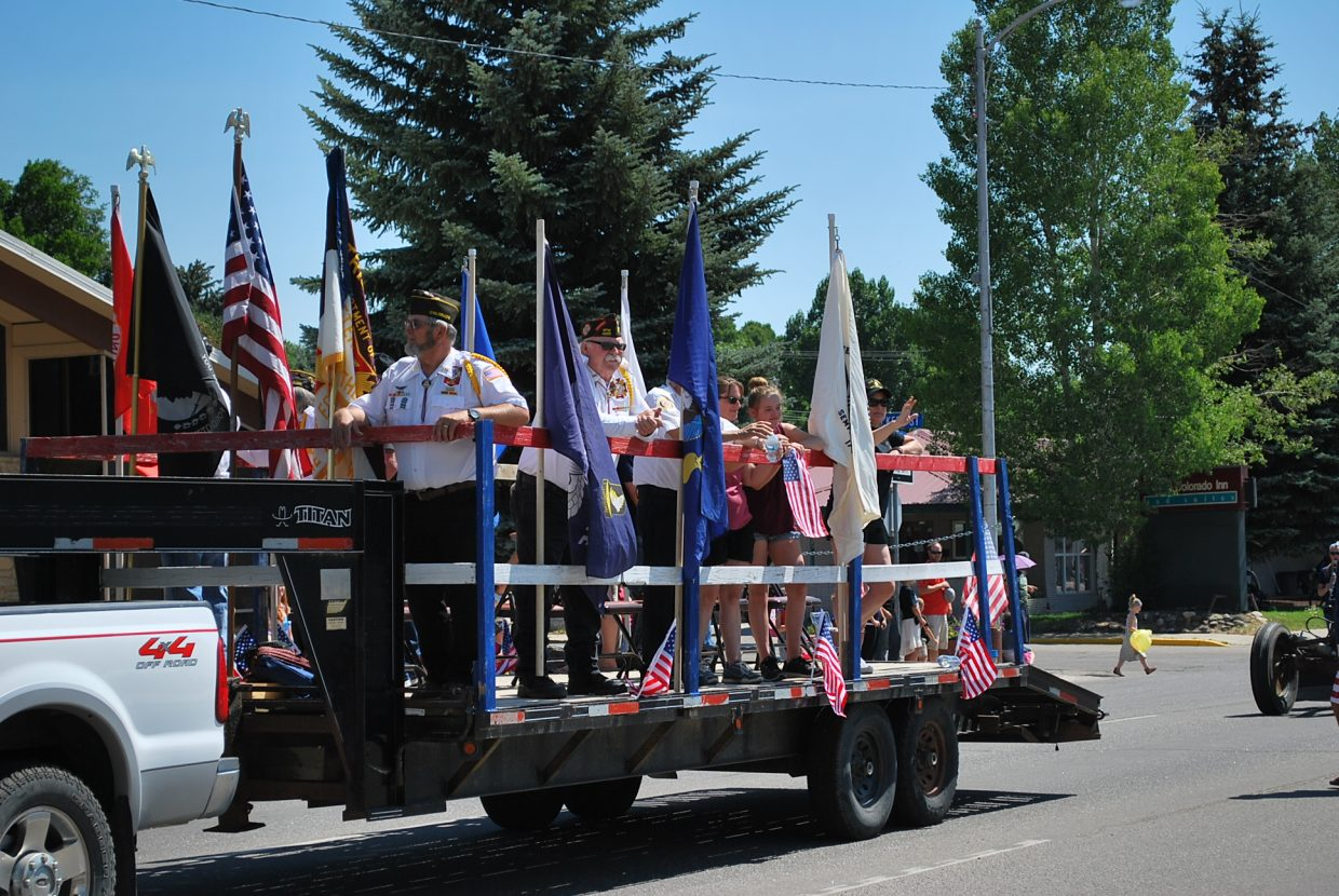Veterans and their family wave from their float to parade goers.