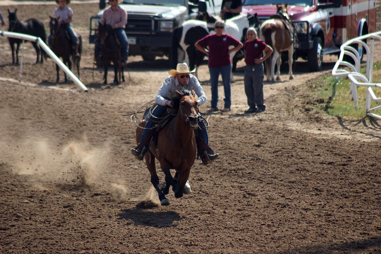 Joe Wood, from Meeker, and his horse, Spud, race past race officials and volunteers setting the winning pace in the inaugural Derby Days at the 100th Moffat County Fair on Sunday, Aug. 12.
