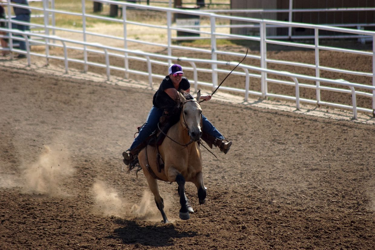A cowgirl urges her horse — used to chase down cattle or sheep — to race faster.