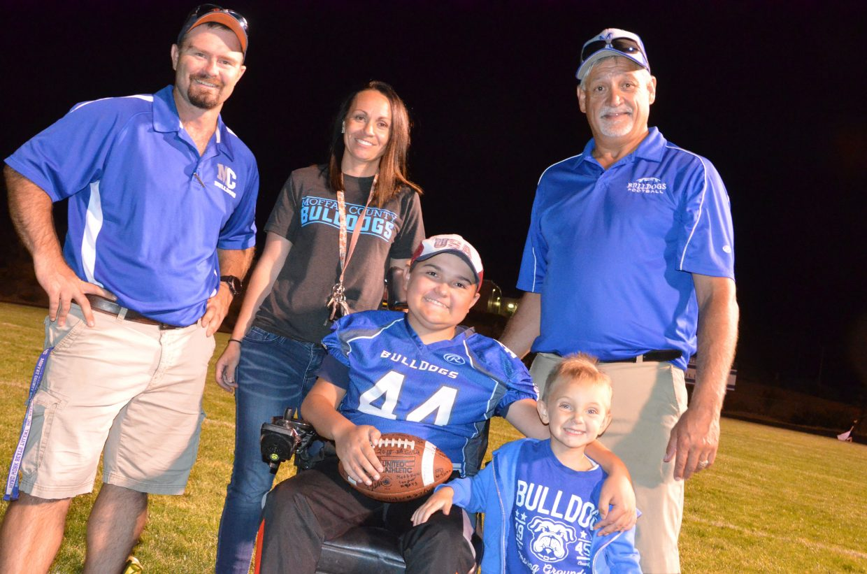 Craig Middle School's JP Price, center, is joined by football coach Dusty Vaughn, CMS Athletic Director Sara Linsacum, coach Tony Maneotis and Maneotis's grandson Easton Mixon following Tuesday's football games at Moffat County High School. Besides two wins for the middle school Bulldogs against Steamboat Springs on the high school field, Price rushed for a touchdown.