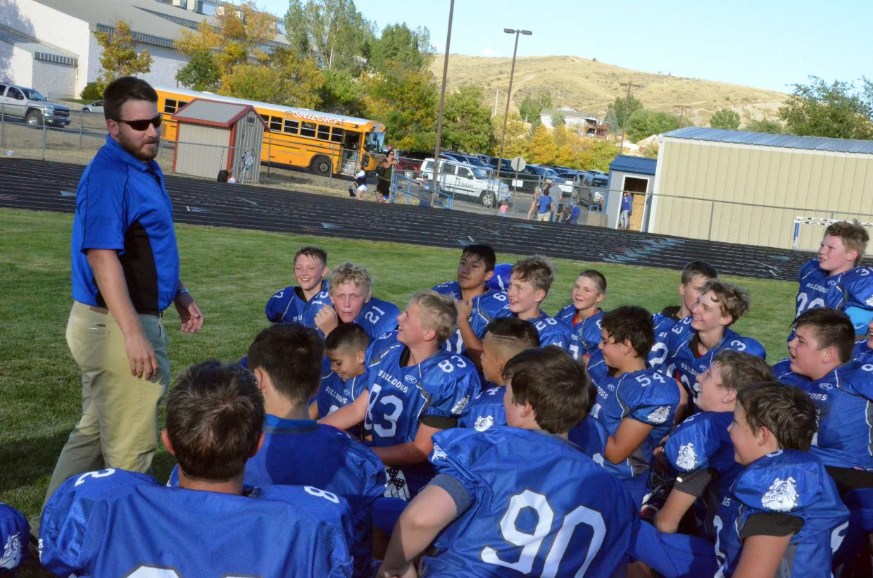 Craig Middle's School seventh-grade football coach Brice Smith congratulates CMS players on a win against Steamboat Springs.